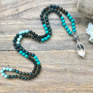 This is a peaceful and soothing Mala Necklace that reminds me of stunning beaches and pristine oceans. The stones work together to open the throat chakra, which boosts clear communication and self-expression by drawing negativity from the body. This mala Bead Necklace is made with chrysocolla, turquoise, smoky quartz and matte amazonite 8mm beads and the guru is a sterling silver Bali bead and a large smooth Crystal Quartz as a touch stone and to amplify all the energies.