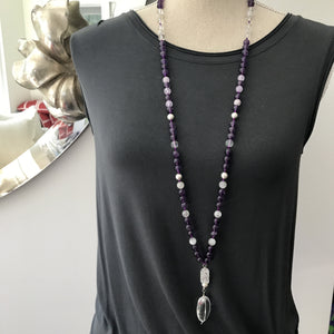 "This Mala necklace is made of amethyst stones, white moonstones, crystal quartz, sterling silver brushed beads, a rutilated quartz bead and a large, oval crystal quartz smooth guru bead . This Mala is lovingly knotted every three beads with natural silk. It measures aprox. 18"" long without the guru bead. The stones are 8 mm."