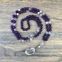 "Load image into Gallery viewer, This Mala necklace is made of amethyst stones, white moonstones, crystal quartz, sterling silver brushed beads, a rutilated quartz bead and a large, oval crystal quartz smooth guru bead . This Mala is lovingly knotted every three beads with natural silk. It measures aprox. 18"" long without the guru bead. The stones are 8 mm."