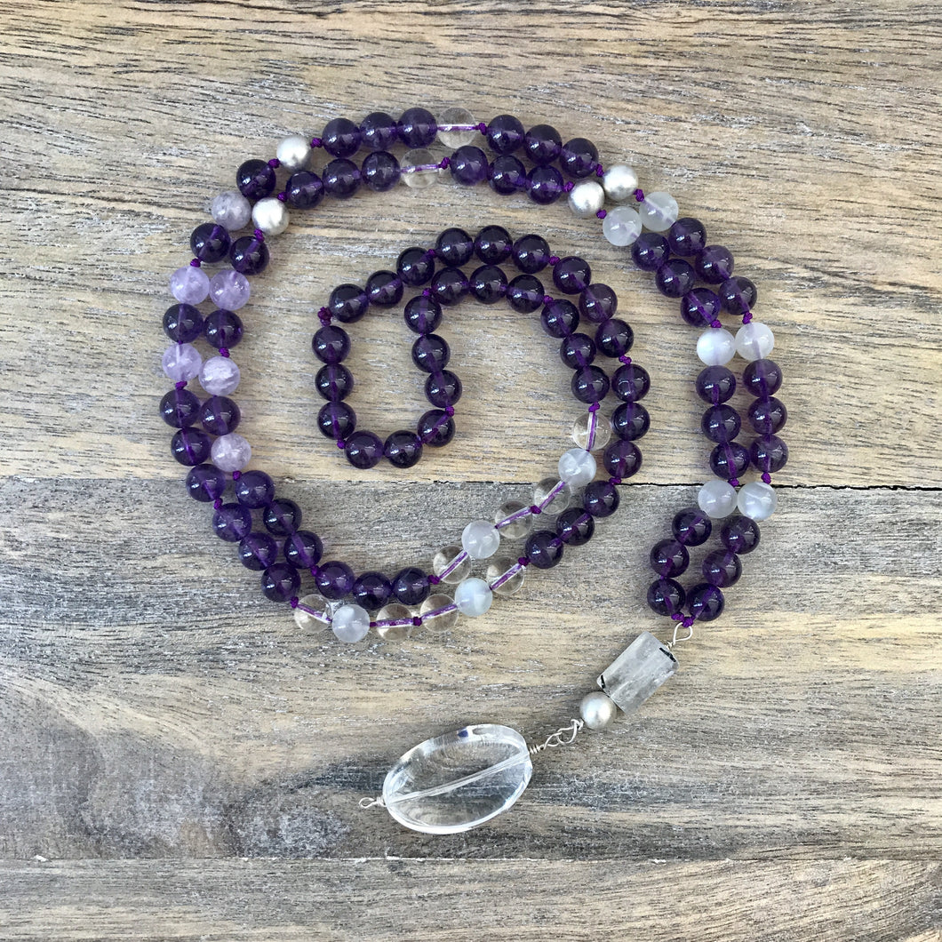This Mala necklace is made of amethyst stones, white moonstones, crystal quartz, sterling silver brushed beads, a rutilated quartz bead and a large, oval crystal quartz smooth guru bead . This Mala is lovingly knotted every three beads with natural silk. It measures aprox. 18