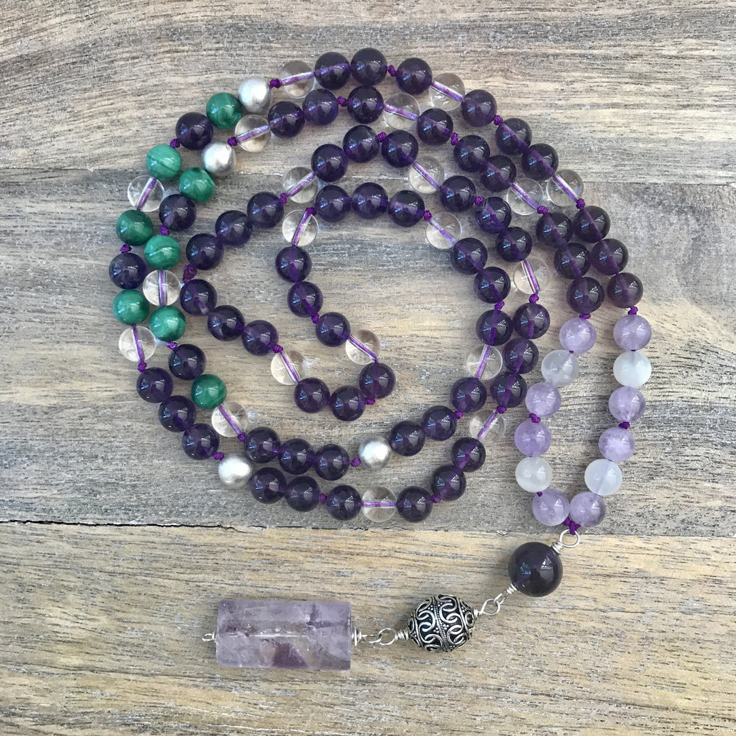 This Mala necklace is made of amethyst stones, white moonstones, malachite, crystal quartz, sterling silver brushed beads, a silver bali bead and a large lavender amethyst guru bead. This Mala is lovingly knotted every three beads with natural silk. It measures aprox. 18