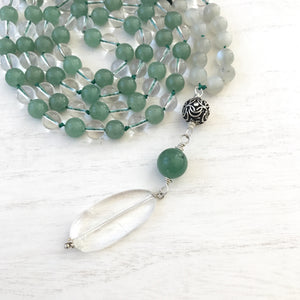 "This Mala necklace is made of green aventurine, moonstone, a bali bead and crystal quartz. This Mala is lovingly knotted every three beads with natural silk. It measures 18"" long without the guru bead. The stones are 6mm."