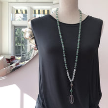 "Load image into Gallery viewer, This Mala necklace is made of green aventurine, moonstone, a bali bead and crystal quartz. This Mala is lovingly knotted every three beads with natural silk. It measures 18"" long without the guru bead. The stones are 6mm."