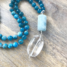 Load image into Gallery viewer, This Mala necklace features Aquamarine, blue apatite and moonstone beads, plus the guru bead which is made of a beautiful, large aquamarine and a large Crystal Quartz bead.