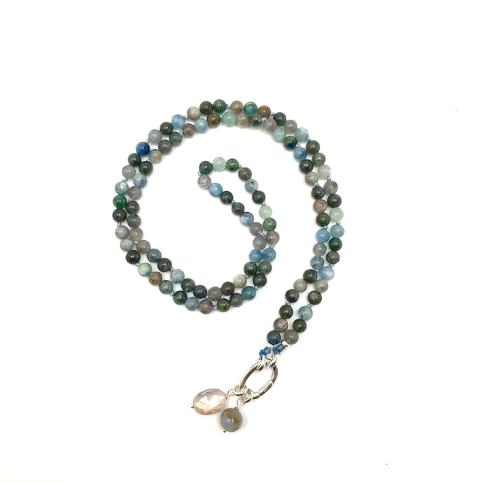 These beads have a beautiful mix of light and dark blue. The mala comes with a Crystal Quartz charm like the one pictured (other charms are for show only and can be purchased separately).