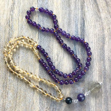 Load image into Gallery viewer, This Mala necklace features amethyst and citrine plus the guru bead which is made with a round onyx bead, a large and smooth amethyst stone and a beautiful rutilated quartz stone all hand wired with .925 Sterling Silver.  This Japa Mala can help you with an emotional or spiritual aspect that you want to work on either through meditation or your everyday life. You can also wear it or carry it with you to help you in your spiritual journey and as a reminder to live in the moment.