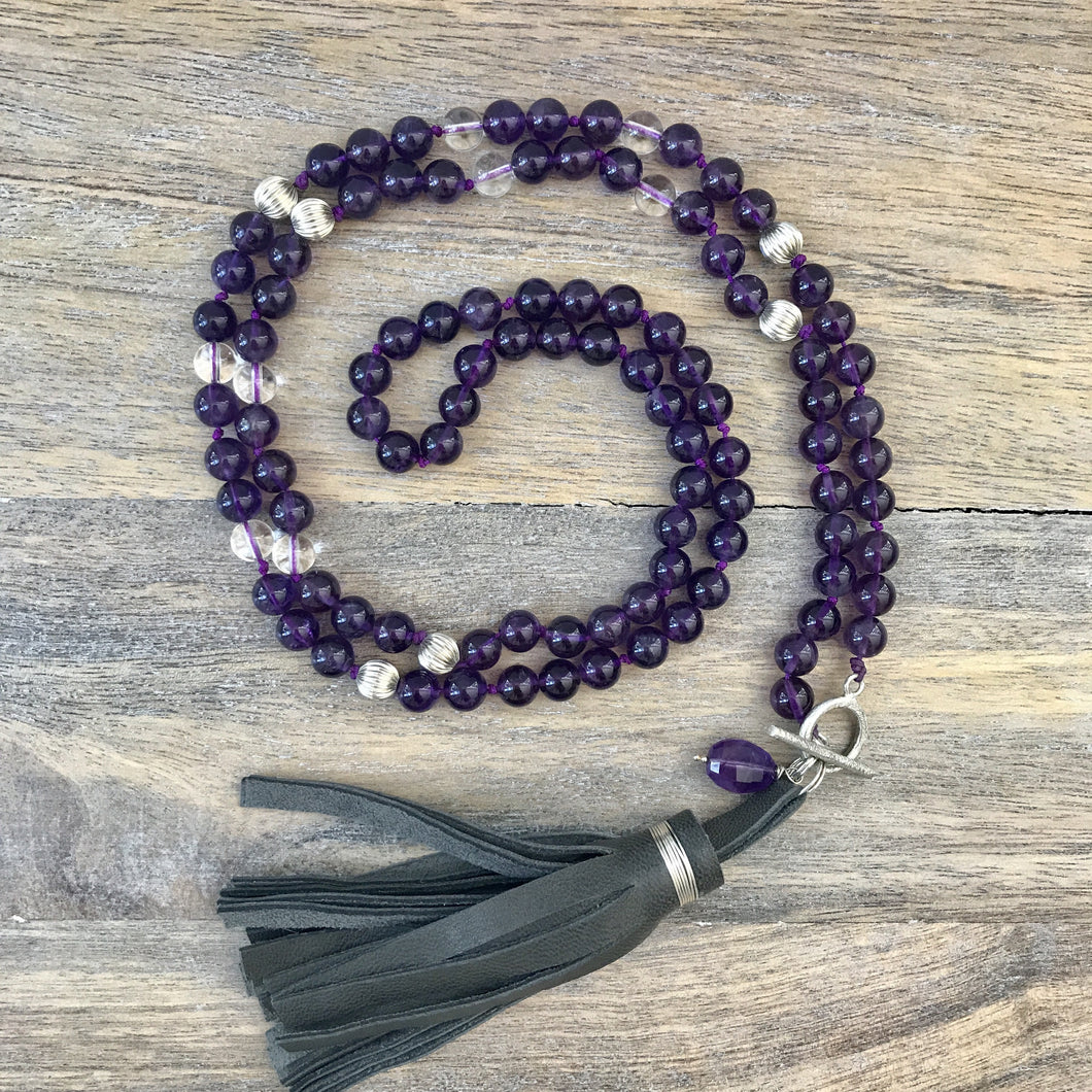 This is a special, Limited Edition Mala. It features 108 gemstone beads for your meditation practice or as an intention necklace. It features a sterling silver toggle clasp that allows you to wear it long or doubled as a fashion statement. At the bottom, a soft grey leather tassel and an oval amethyst stone, add a special touch.