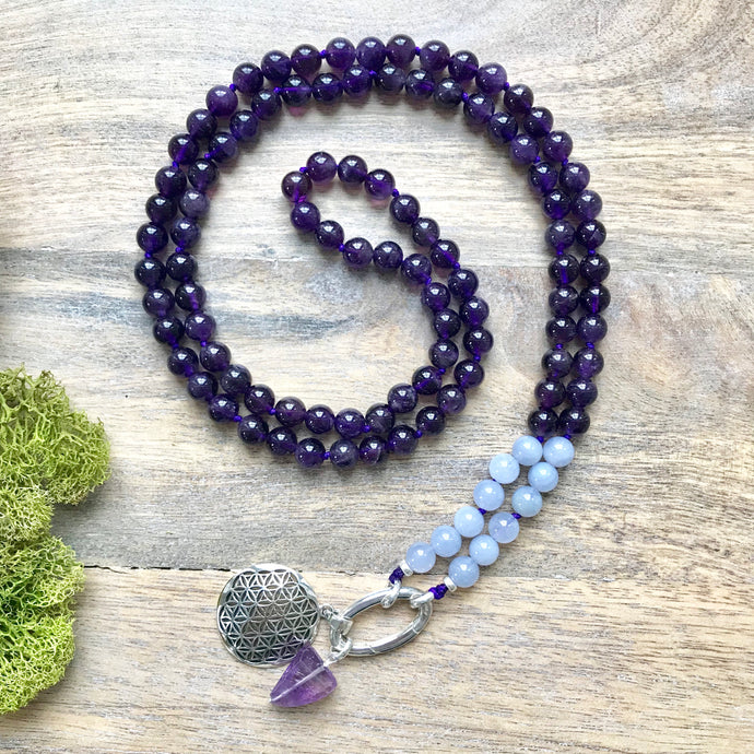This Mala necklace is made of amethyst and chalcedony. This Mala is lovingly knotted every three beads with a strong nylon cord. It measures 18.5