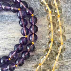 This Mala necklace features amethyst and citrine plus the guru bead which is made with a large round amethyst bead, a large and smooth crystal quartz stone all hand wired with .925 Sterling Silver.