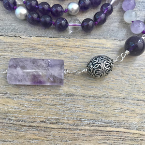 "This Mala necklace is made of amethyst stones, white moonstones, malachite, crystal quartz, sterling silver brushed beads, a silver bali bead and a large lavender amethyst guru bead. This Mala is lovingly knotted every three beads with natural silk. It measures aprox. 18"" long without the guru bead. The stones are 8 mm."