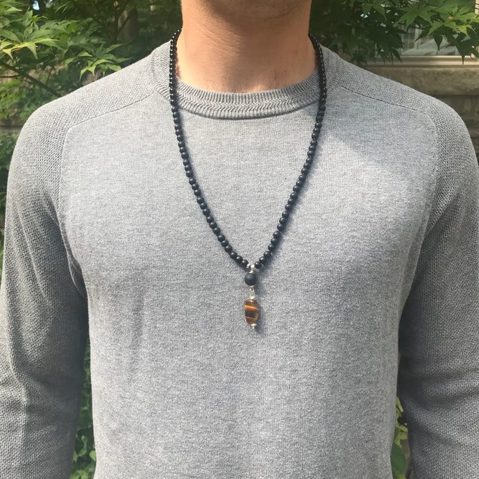 This mala necklace features 6mm Black Onyx and matte Black Obsidian beads. The guru is handwired with .925 Sterling Silver and features a round Lava bead followed by an oblong Tiger Eye bead.