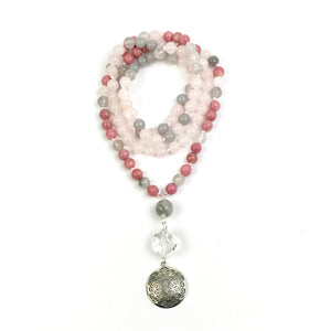 This mala necklace features 108, 8mm Rose Quartz, Rhodonite, Grey Agate, and Rutilated Quartz beads. The guru is made of a round Grey Rutilated Quartz bead, a cut Crystal Quartz and a .925 Sterling Silver Flower of Life charm, all hand wired with .925 Sterling Silver.