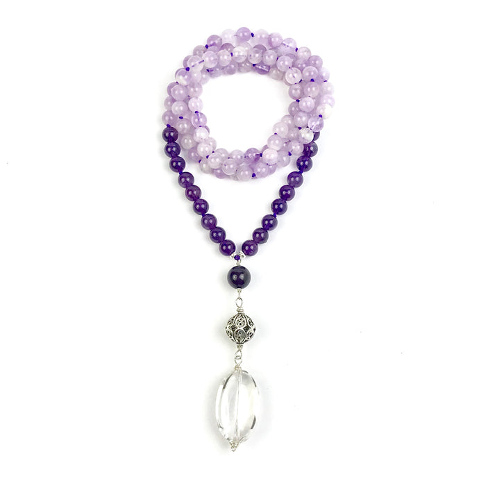 This mala necklace is made of 108, 8mm Amethyst gemstones in two tones plus the guru which is made of a round Amethyst bead, a sterling silver Bali bead, and a large, smooth crystal quartz stone all hand wired with .925 Sterling Silver. This large crystal quartz bead makes for the perfect touch stone.