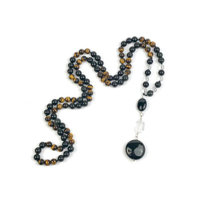 "This Mala necklace is made of tiger eye, black obsidian and crystal quartz. Tiger eye will help you stay optimistic and will assist you in accomplishing your goals. It will be a constant reminder that you can do whatever you set your mind to. Black obsidian is the perfect partner because it's grounding and supporting.  This Mala is lovingly knotted every three beads with natural silk. It measures 18"" long without the guru bead. The stones are 8 mm."