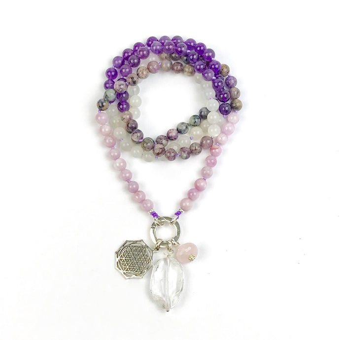 This mala necklace was created with beautiful 8mm Kunzite, Charoite, Amethyst and Moonstone beads. It comes with a Crystal Quartz charm like the one pictured (other charms are for show only and can be purchased separately).