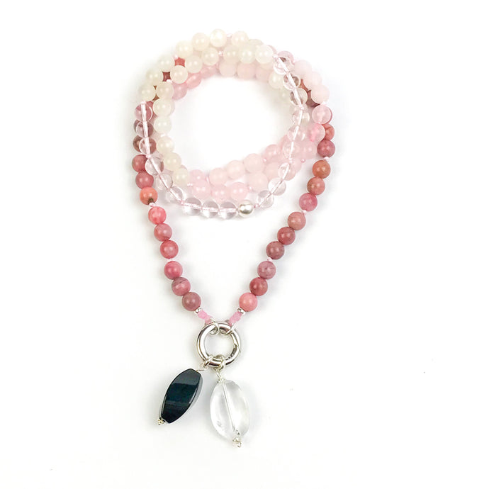 This mala necklace was created with beautiful 8mm polished and matte Rose Quartz, Rhodonite, Moonstone, and Crystal Quartz beads, along with a brushed Sterling Silver bead indicating the midpoint. It comes with a Crystal Quartz charm like the one pictured (other charms are for show only and can be purchased separately).