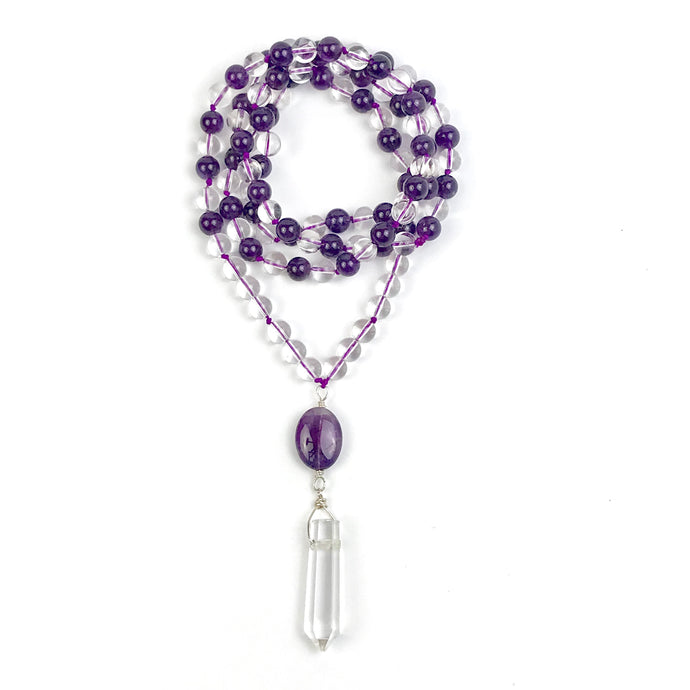 This Mala necklace is made with Amethyst and Crystal Quartz and the Guru bead is made with Amethyst, followed by a Silver Bali Bead and a Crystal Quartz point.