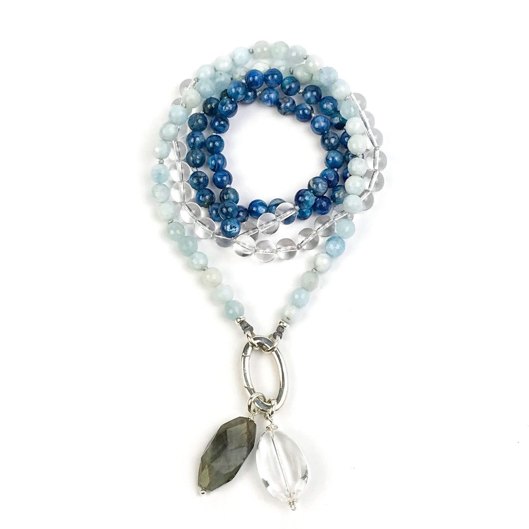 This mala necklace was created with beautiful 7mm Kyanite, Aquamarine, and Crystal Quartz beads. It comes with a Crystal Quartz charm like the one pictured (other charms are for show only and can be purchased separately).