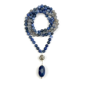 This Mala necklace features Sodalite and Grey Agate beads, plus the guru bead which is made with a sterling silver Bali bead and a large, oval blue agate stone all hand wired with .925 Sterling Silver.