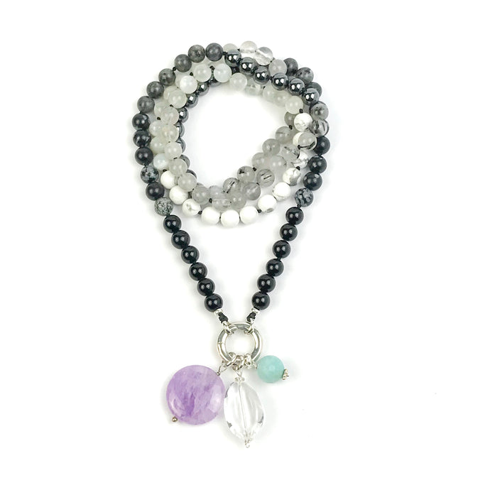 This mala necklace was created with beautiful 8mm Onyx, Snowflake Obsidian, Black-Grey Rutilated Quartz, Hematite, Howlite, Larvikite, and Moonstone beads. It comes with a Crystal Quartz charm like the one pictured (other charms are for show only and can be purchased separately).
