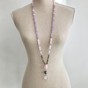 This mala necklace is made of 108, 8mm Rose Quartz, Lavender Amethyst and Grey Moonstone beads, knotted every 3 stones with a strong nylon cord. It features a guru made of a large and unique oval pink opal, followed by a large sterling silver Bali bead and a large, smooth crystal quartz, all hand wired with .925 Sterling Silver.