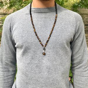 This mala necklace features 6mm frosted matte Tiger Eye and Black Lava beads. The guru is handwired with .925 Sterling Silver and features round Smoky Quartz and Tiger Eye beads.