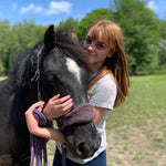 Red head girl cuddling pony. girls arms wrapped around a black ponies neck. supporting mental health awareness. mindful thinking and animal therapy can really help people with mental health issues.