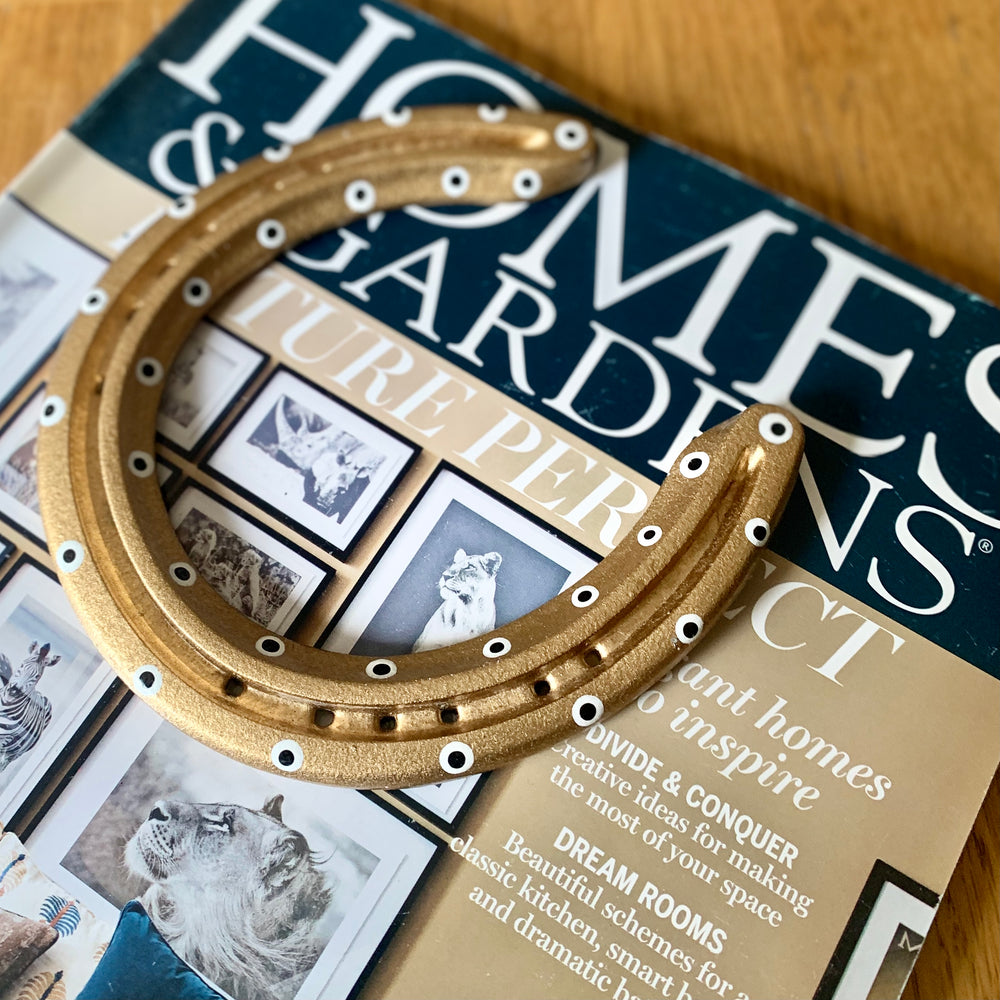 Black and gold horseshoe gifts as ornamental paperweights on magazines. this horshoe gift lays upon Homes & Garden magazine, Britains best interior design journal