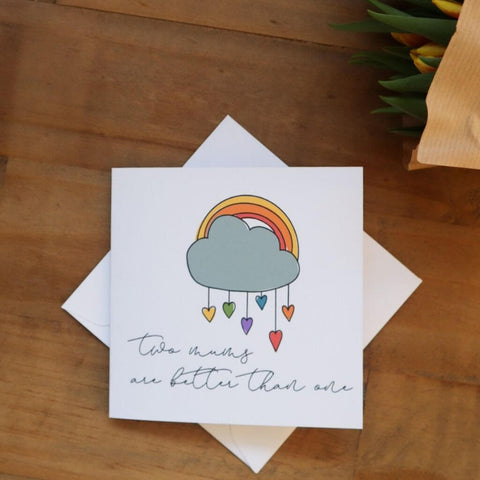 Two mums are better than one card with a rainbow, cloud and raindrop hearts.