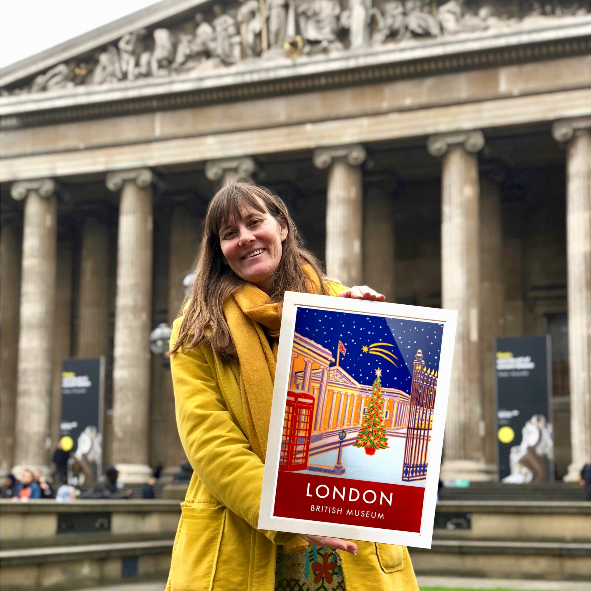Artist Joanne Short outside the British Museum in London holding one of her new art prints of the museum which forms part of the new range of licensed art products featuring Joanne Short's art.