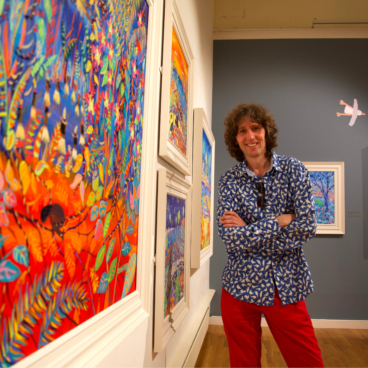 Artist John Dyer standing next to his painting of the Amazon rainforest spirits in Falmouth Art Gallery