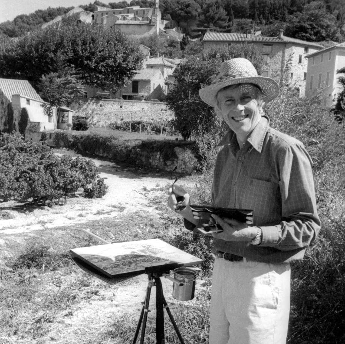 Ted Dyer at work in Provence painting at his easel in a vineyard in the village of Gigondas