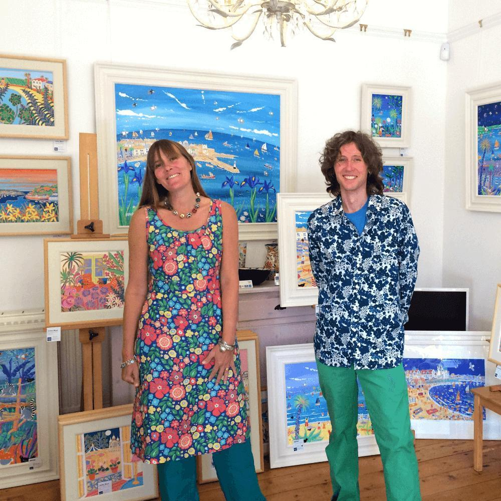Cornish artists Joanne Short and John Dyer standing in The John Dyer Gallery in Cornwall surrounded by original paintings of Cornwall