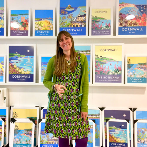 Cornish artist Joanne Short standing in front of her acclaimed vintage style art posters of Cornwall