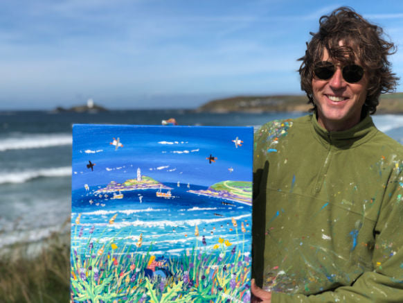Artist John Dyer on the cliffs at Gwithian holding his painting of Godrevy lighthouse