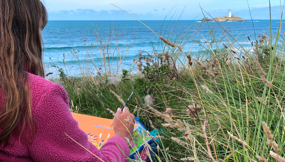 Cornish artist Joanne Short at work on a painting of Gwithian and Godrevy lighthouse.