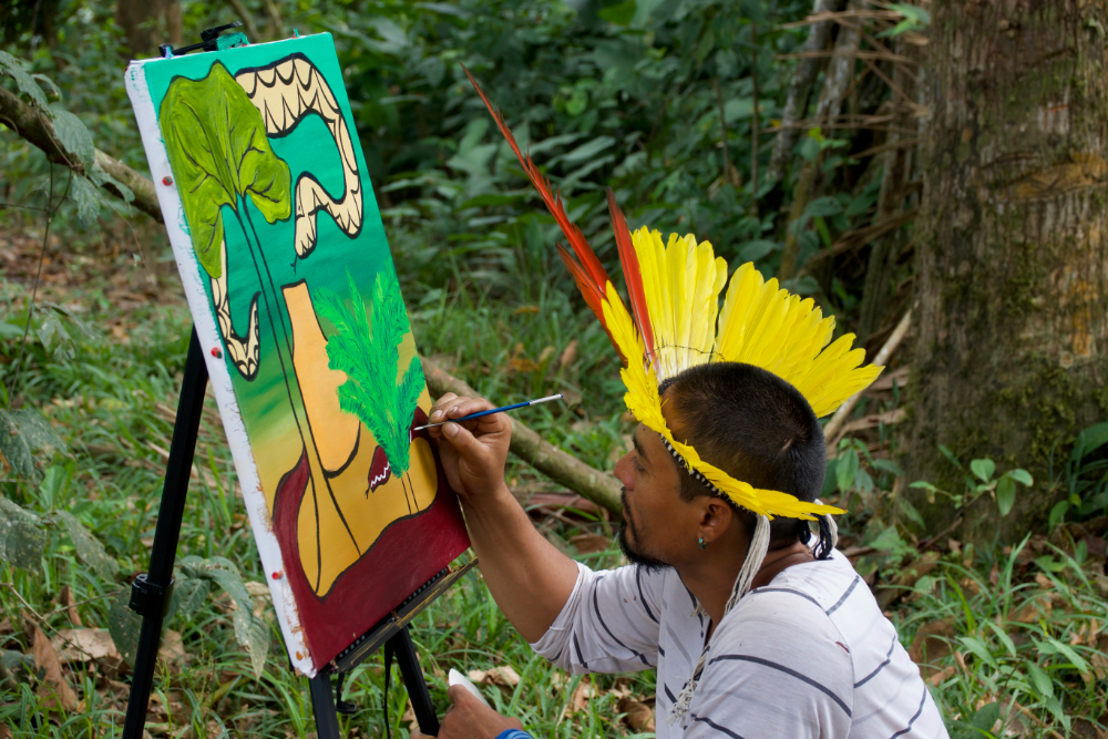 Amazon Indian artist Nixiwaka Yawanawá painting in the Amazon rainforest.