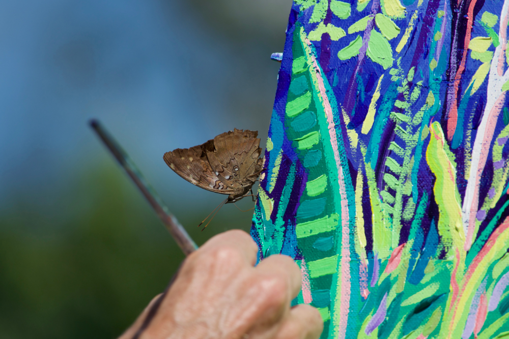 An Amazon rainforest butterfly rests on the edge of John Dyer's painting as he paints deep in the jungle