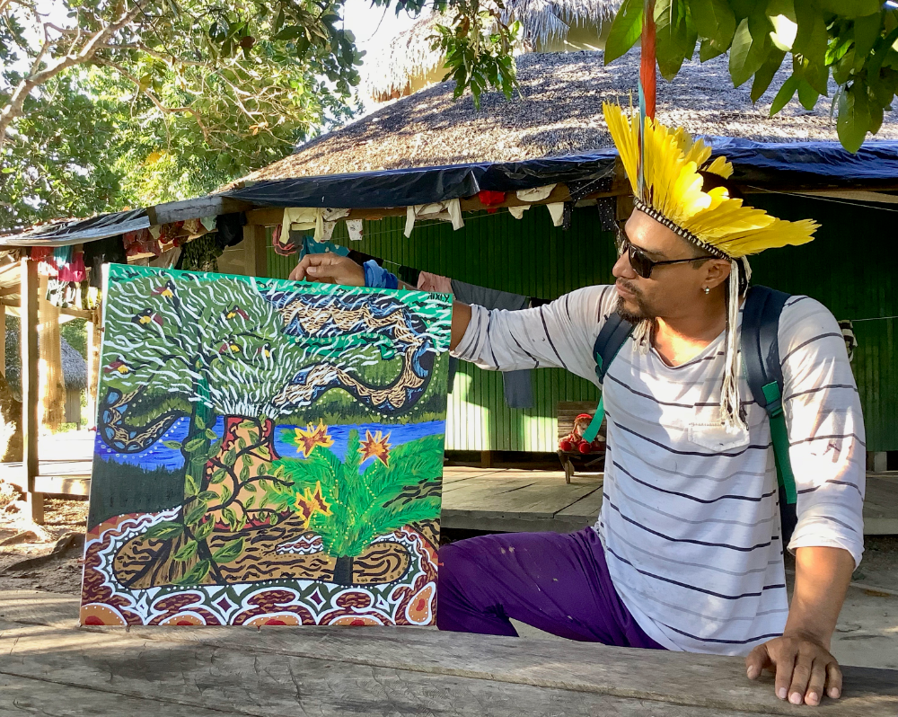 Nixiwaka Yawanawá with his finished painting in the tribal village of Mutum deep in the Amazon rainforest of Brazil.