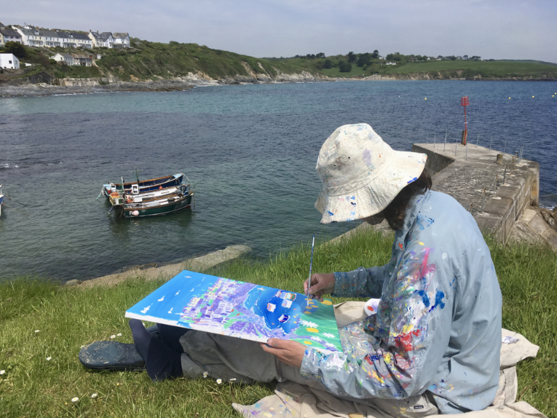 Artist John Dyer at work on his painting 'Summer Days, Portscatho' in the Cornish fishing village of Portscatho in Cornwall.