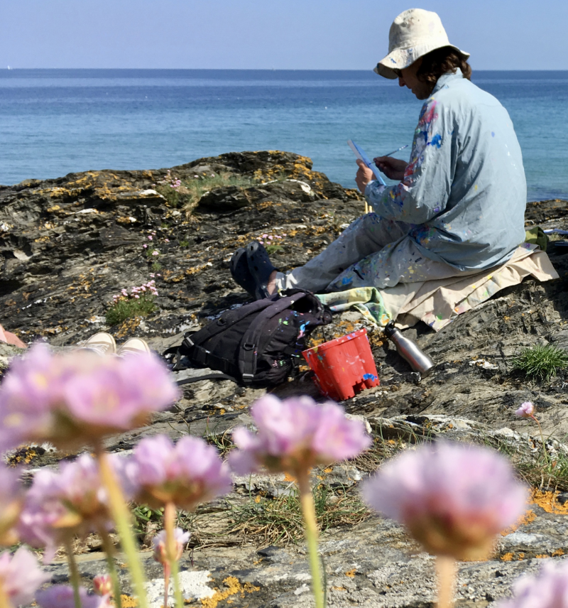 Artist John Dyer at work sitting on the rocks and painting the Roseland in Cornwall. Sea pinks in the foreground