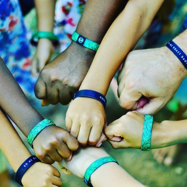 Support Humanity and Hope this Holiday Season with your purchase of this Hope Lives in Us Refocus Band.