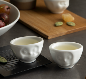 Set of two egg cups in white from the TASSEN product family of fun dishware by FIFTYEIGHT Products. Set features two egg cups in white, featuring 'Oh please' and 'tasty' facial expressions. Dishwasher and microwave safe bowls. Shipped in exclusively designed gift box.