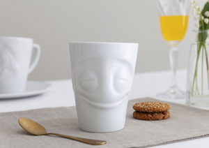 Coffee mug with 'cheery' facial expression and 11 oz capacity. From the TASSEN product family of fun dishware by FIFTYEIGHT Products. Tall coffee cup with handle in white, crafted from quality porcelain.