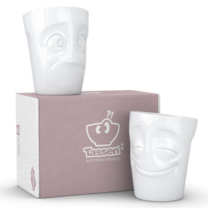 Set of two coffee mugs with 'Cheery' and 'Baffled' facial expression and 11 oz capacity. From the TASSEN product family of fun dishware by FIFTYEIGHT Products. Tall coffee cups without handles in white, crafted from quality porcelain.