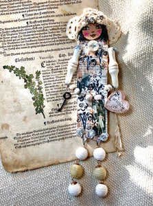 "'""Curiosity,"" a mixed media collaged doll"