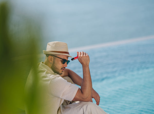 Man with a vape is sitting near the ocean