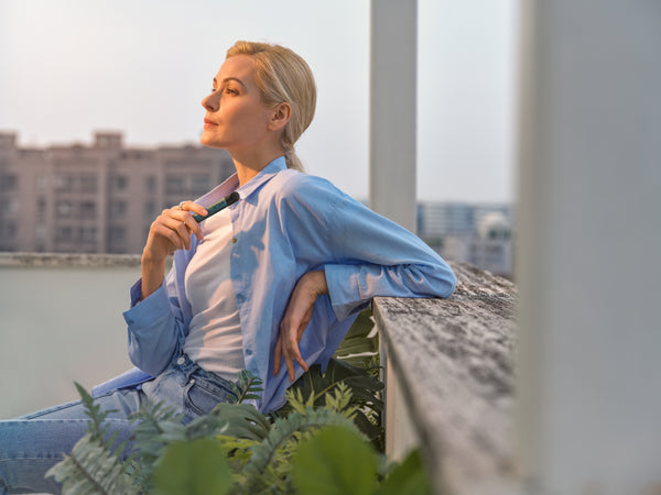 Woman relaxing on the rooftop while holding RELX Infinity device and gazing at the distance