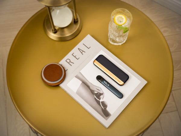 A RELX vape device and slim-fit charging case displayed on a magazine with a paperweight, glass of beverage and hourglass.