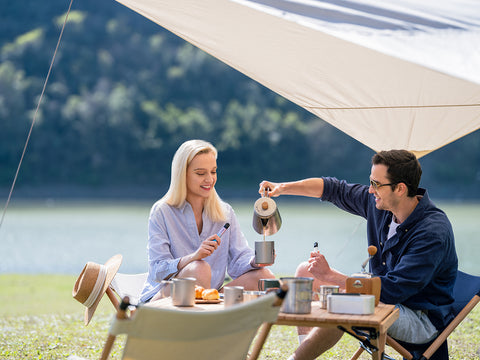 A man and woman sitting under a canopy while enjoying tea and pastries together, and holding a RELX vape device in their hands.